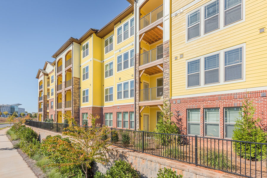 Ballantyne apartment exterior with fencing, lush landscaping, and apartment balconies.