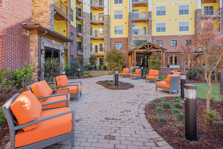 Outdoor courtyard with paver walkways, plush outdoor chairs, and mulch and grass landscaping.