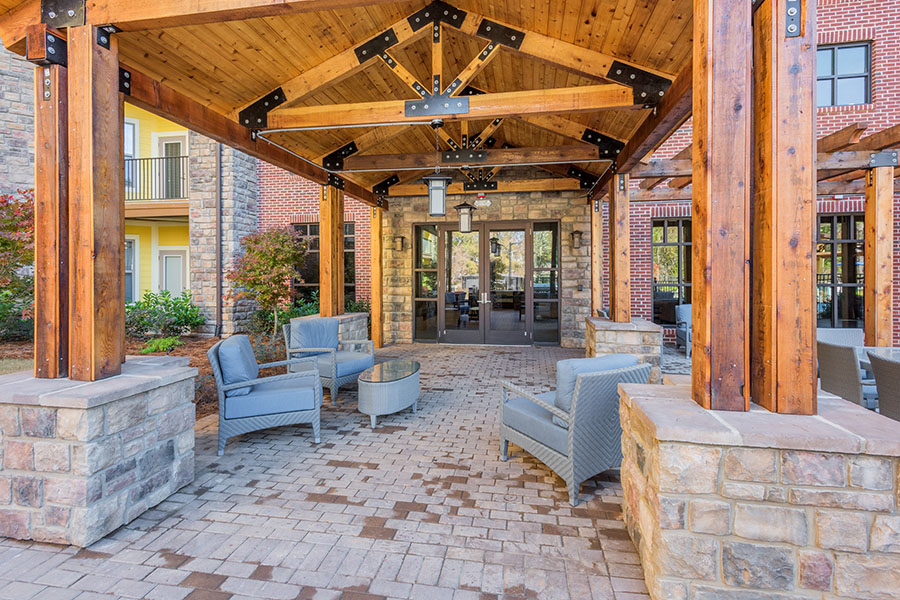 Covered seating area with exposed wood trusses, comfortable plush chairs, and entrance to building.