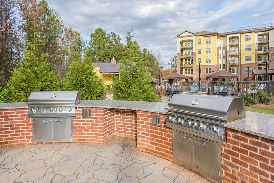 Built in BBQ grill area with paver patio, tall trees, and apartments behind.
