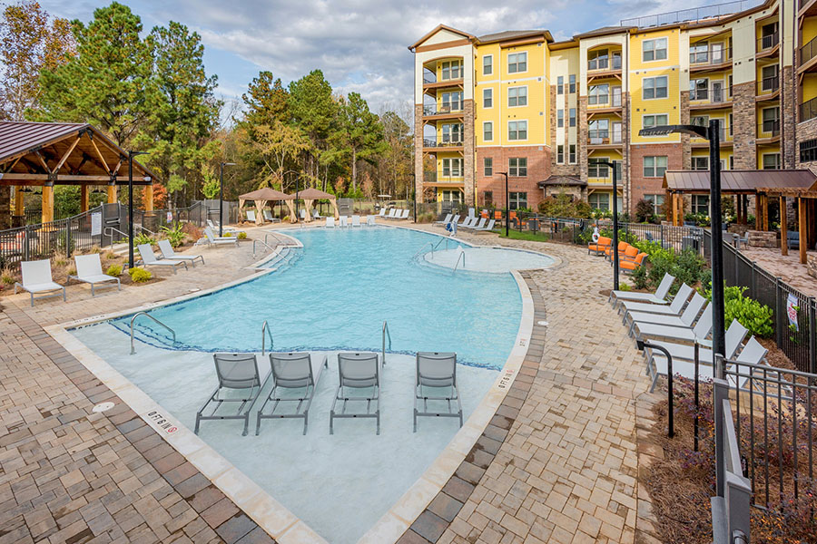 Pool area with paver patio and in-pool lounge chairs overlooked by apartment balconies.
