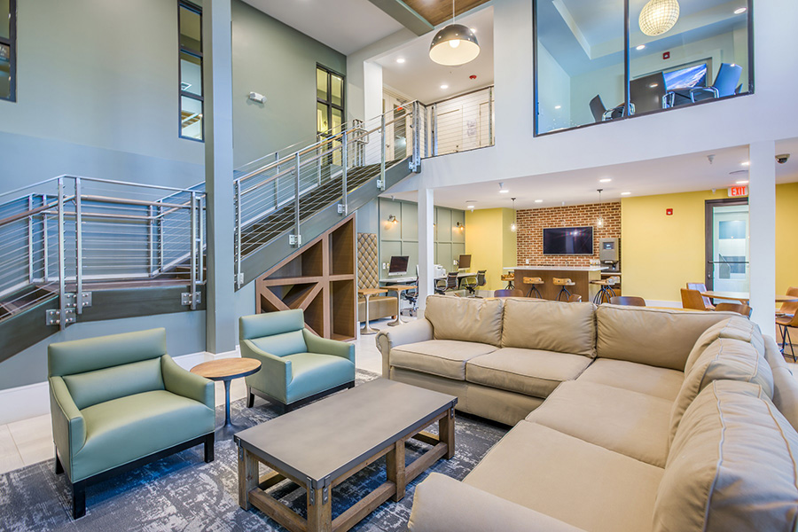 Lounge with high ceilings, large comfortable leather sectional and chairs, and long staircase to second floor.