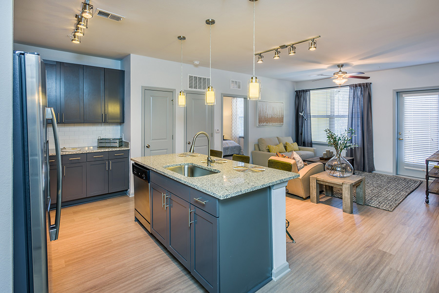 Kitchen with wood floor, gray cabinets, large island with stools, and living room with balcony door behind.