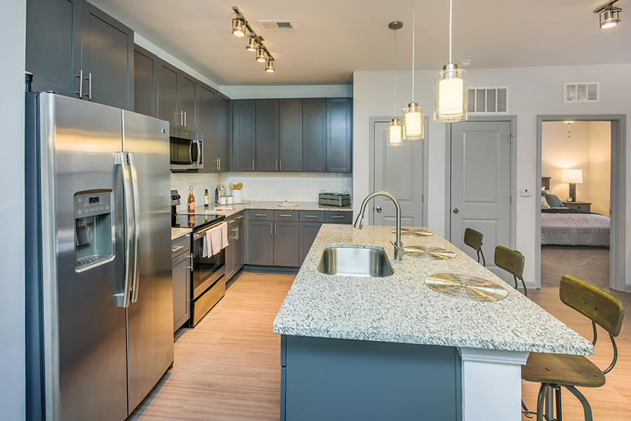 Kitchen with wood floor, large island with stools, gray cabinets, light counters, and stainless steel appliances.