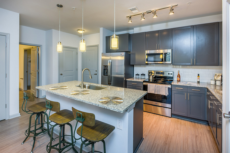 Kitchen with wood floor, large island with stools, gray cabinets, and pendant lights.