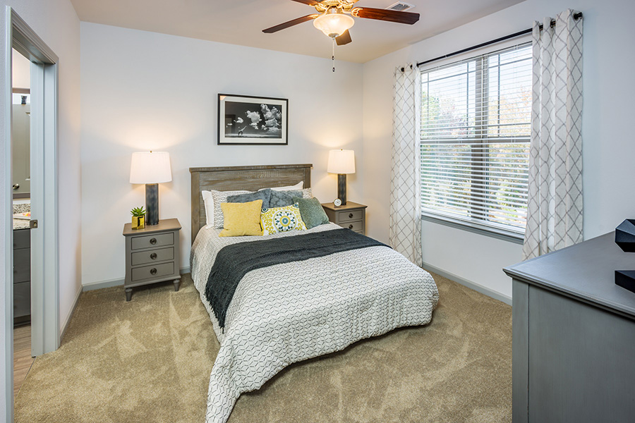 Bedroom with plush carpet, platform bed with comfortable bedding, bedside tables with lamps, ceiling fan, and large window.