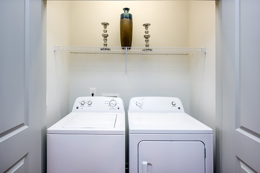 Laundry room with washer and dryer machines and shelf with decorations.