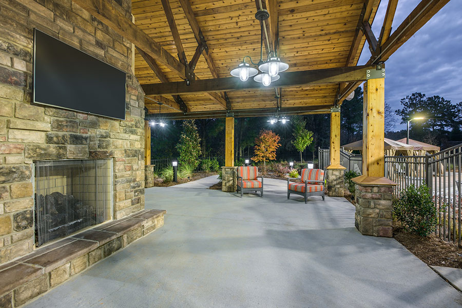 Large outdoor covered seating area with stone fireplace, TV, and comfortable chairs.