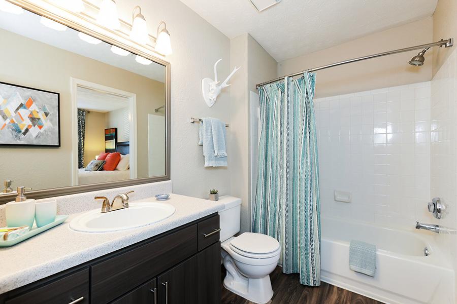 Bathroom with tiled tub/shower, large vanity mirror, dark wood cabinet, white countertop, and hardwood flooring.