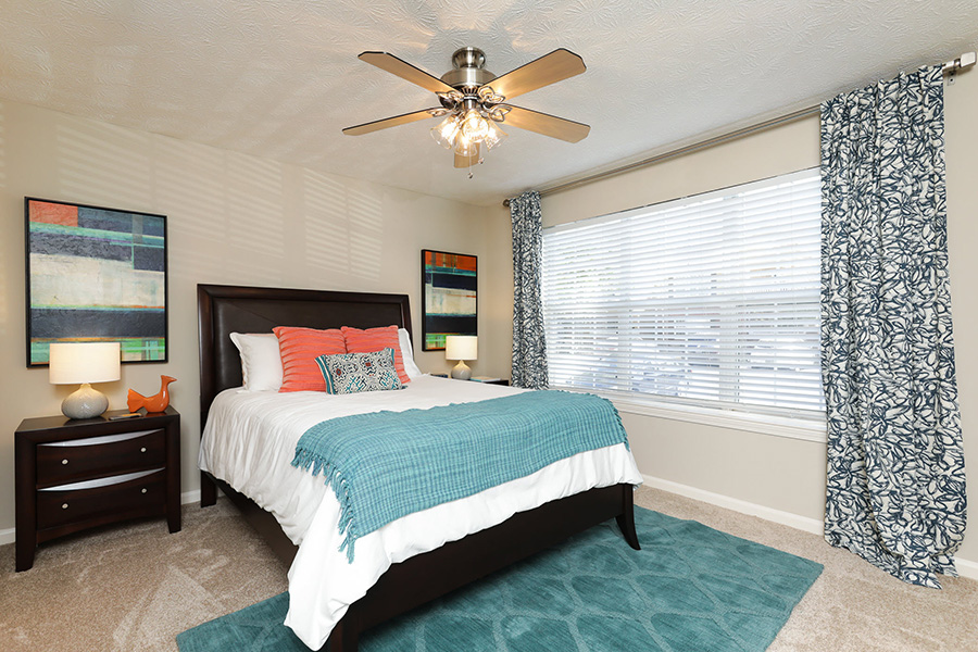 Bedroom with 3 large windows, ceiling fan, carpet flooring, bed, and side tables.