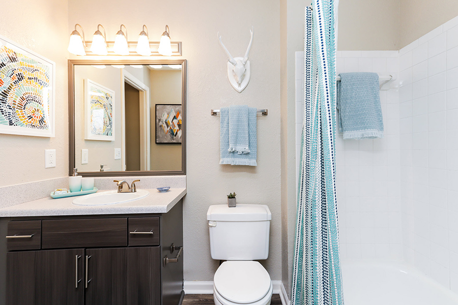 Bathroom with tiled tub/shower, vanity mirror and light, dark wood cabinet, white countertop, and hardwood flooring.