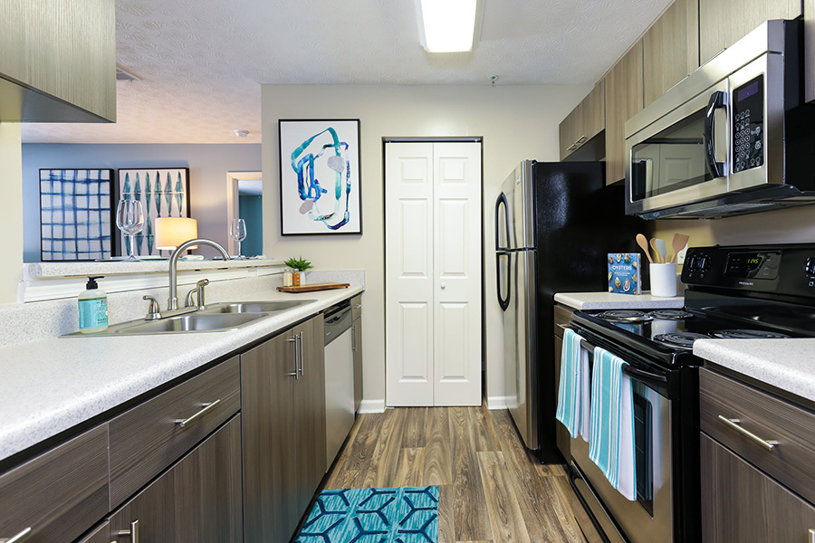 Kitchen with stainless steel appliances, dark wood cabinetry, white countertops, breakfast bar, and pantry.
