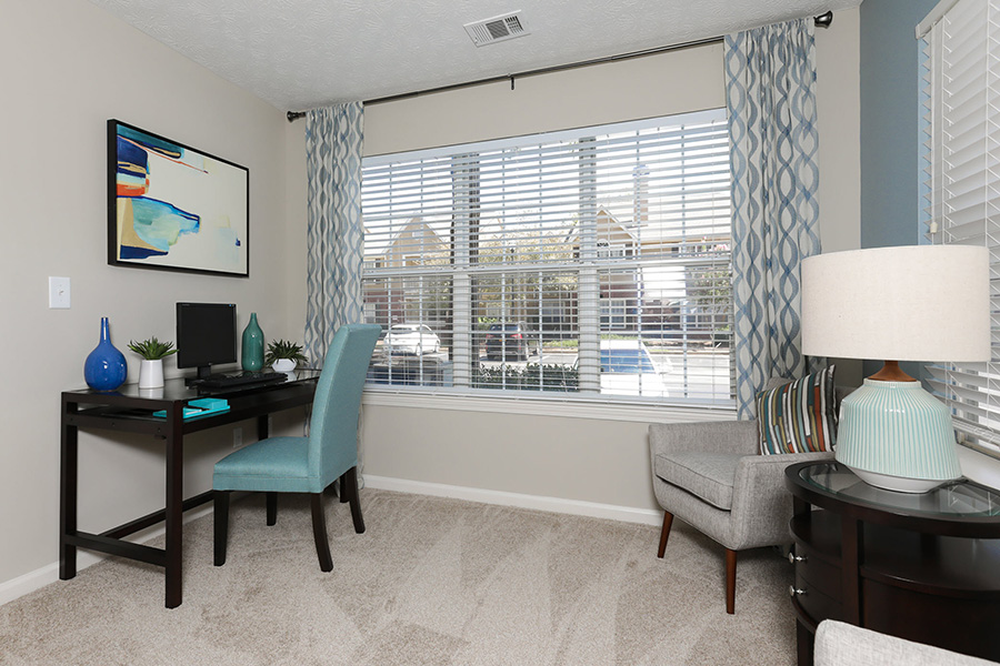 Office room with 3 large windows, carpet flooring, desk and 2 chairs.