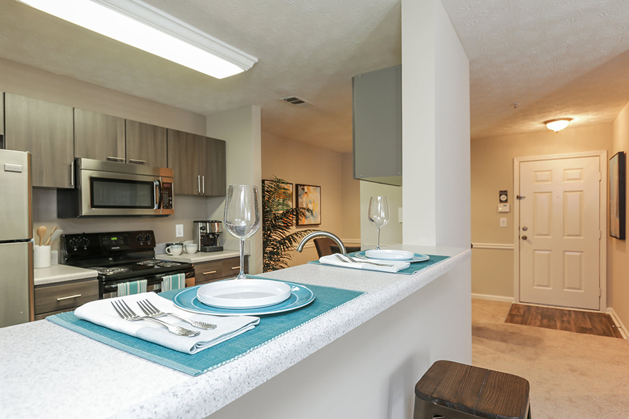 Kitchen with stainless steel appliances, dark wood cabinetry, white countertops, and breakfast bar.