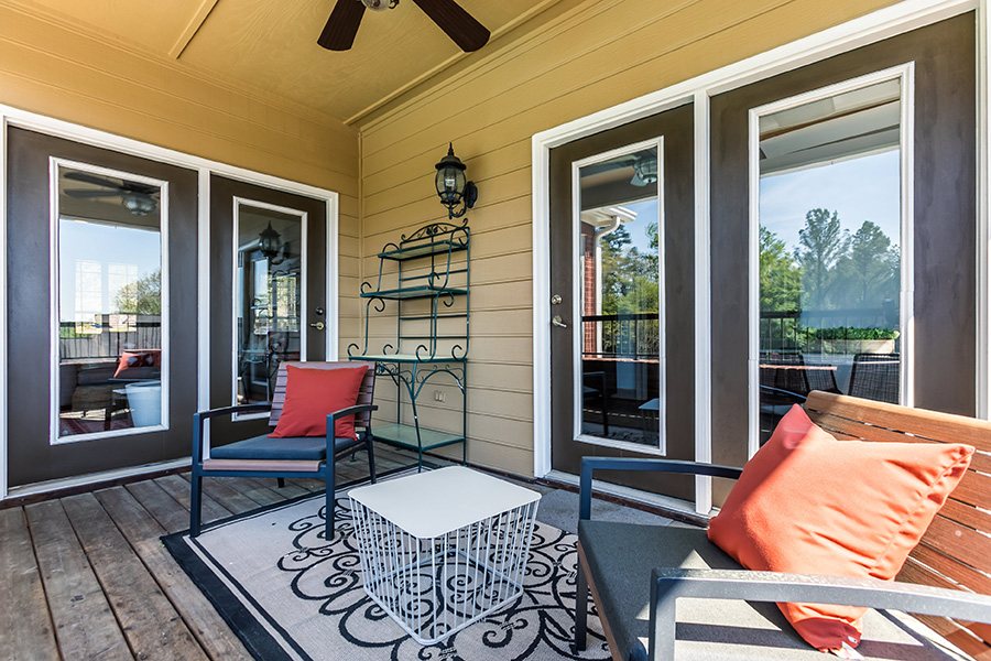 Outdoor patio with wood plank flooring, 2 sets of double doors leading inside, 2 patio chairs, and 1 table.