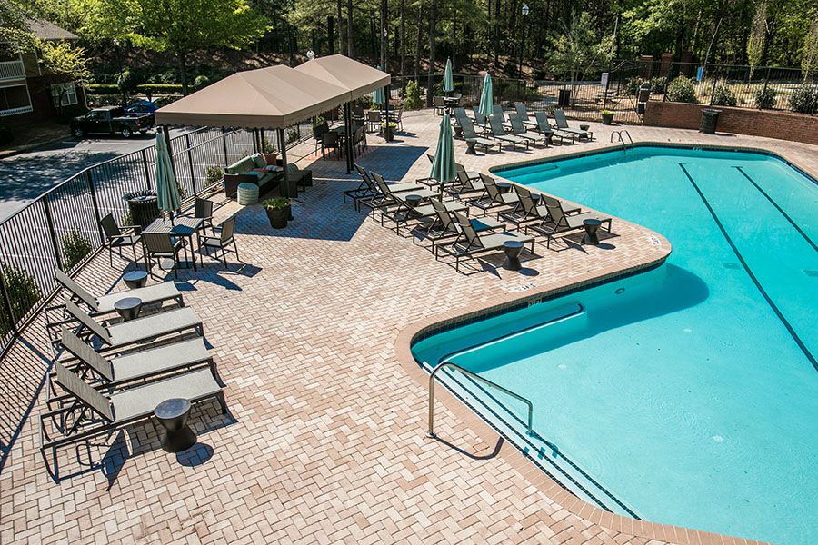 Outdoor community pool with surrounding lounge seating and covered cabana area.