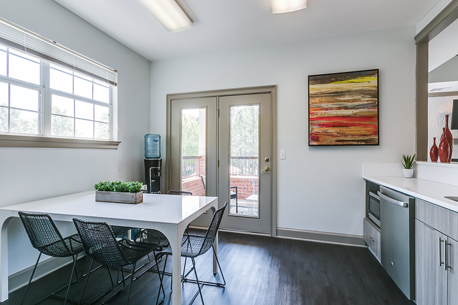 Community kitchen with table and chairs, double doors leading outside, and stainless steel appliances.