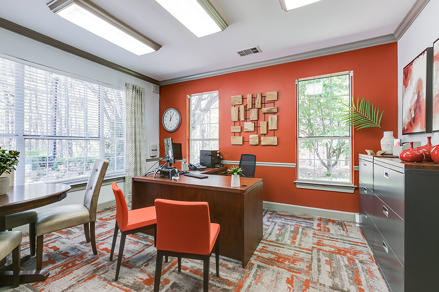 Community leasing office space with desks and chairs and several large windows.