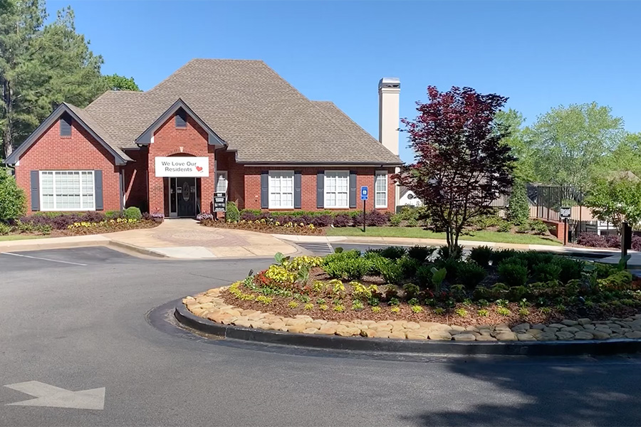 Video tour thumbnail for Alpharetta with round driveway, brick clubhouse, and landscaped property.