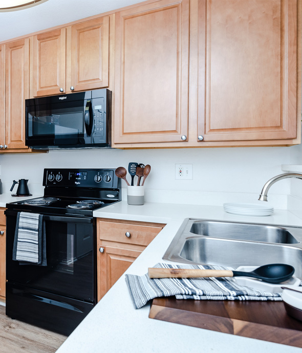 modern kitchen with black appliances and white sleek countertops decorated with dark wood cutting board and wooden spoon