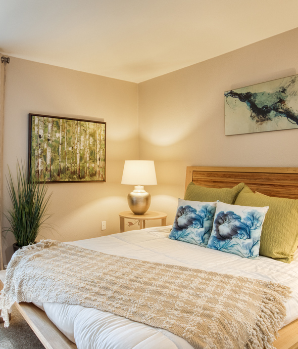 apartment bedroom in warm lighting with a modern wood bed frame and quilted comfortable bedding