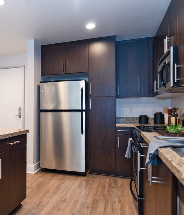 apartment kitchen with updated stainless steel appliances, granite countertops and dark wood cabinets