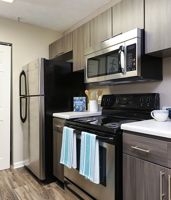 Kitchen with rich wood floors and cabinets, smooth white countertops, and stainless steel appliances.