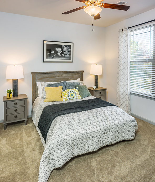 Bedroom with plush carpet, platform bed with comfortable bedding, wood bedside tables with lamps, and large window.