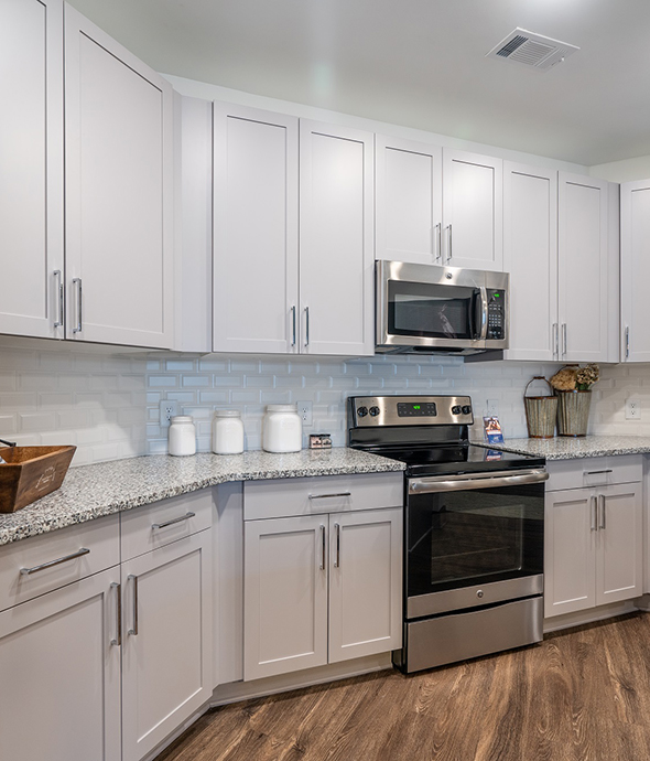 Kitchen with smooth countertops, white cabinets, rich wood floor, and stainless steel appliances.