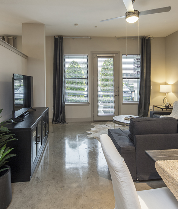 Apartment living room with plush chair, wood entertainment center with TV, and glass door to balcony.
