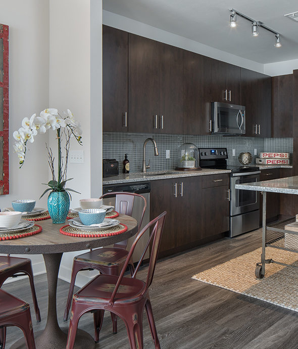Kitchen with rustic metal dining table and chairs, wood floors and cabinets, and stainless steel appliances.