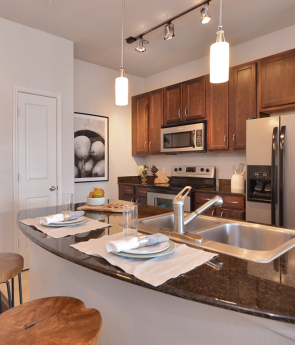 Apartment kitchen with breakfast bar, wood cabinets, stainless steel appliances, and hanging pendant lights.