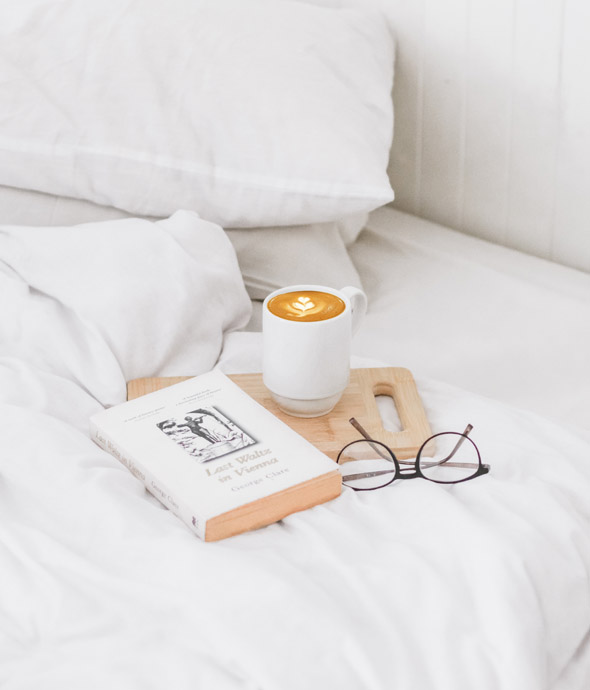 detail of white luxury bed with a book and reading glasses on a wooden tray with a white mug filled with coffee on bed