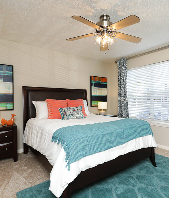 Bedroom with plush carpets, bed with comfortable bedding, wood bedside tables with lamps, and large window.