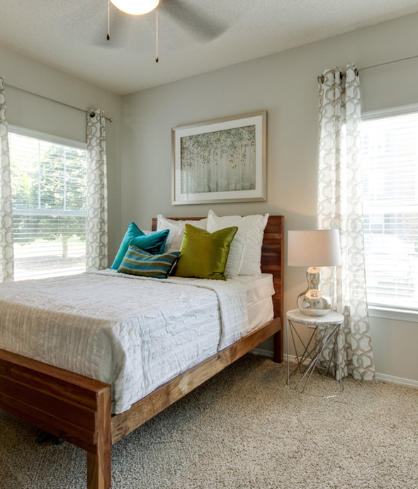 Bedroom with plush carpet, wood bed frame with comfortable bedding, large artwork, and corner windows.