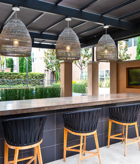 luxury outdoor bar with stone countertops woven basket light covers and woven black barstools