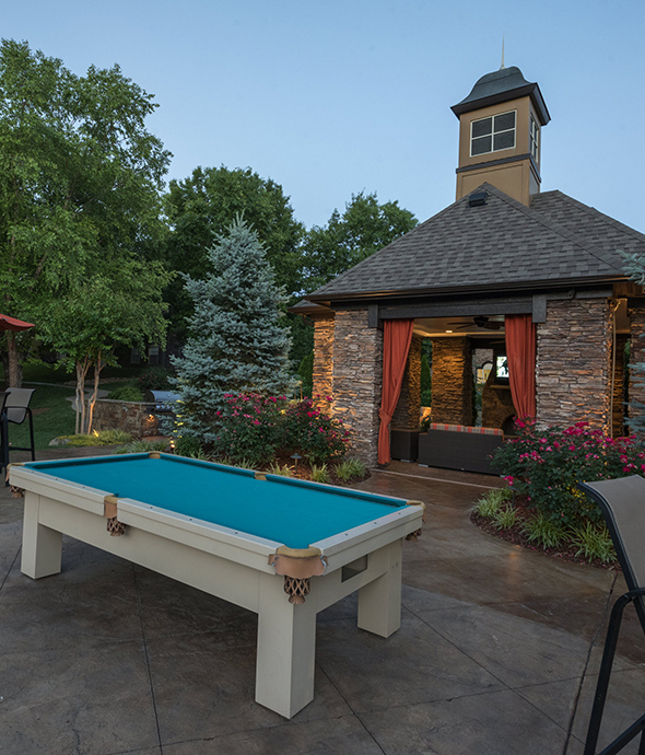 Outdoor area with stone pavers, large brick gazebo, outdoor pool table, and lush landscaping with tall trees.
