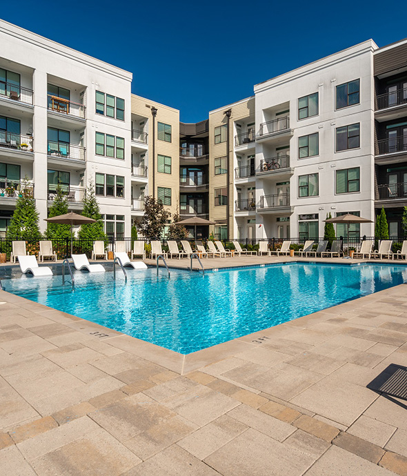 Pool area with stone pavers, bright blue water, and lounge chairs with umbrellas overlooked by apartments.