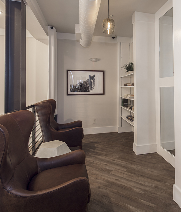 Community lounge mezzanine with wood floors, leather wingback chairs, and built in bookcases.