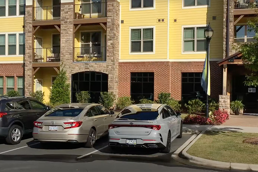 Image for video tour of Ballantyne apartments with parked cars and apartment building with balconies.