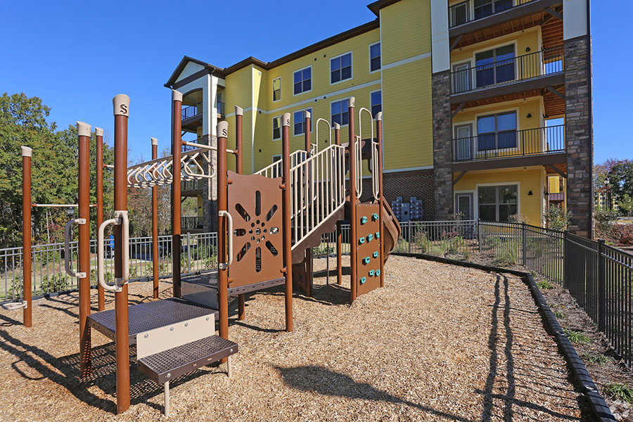 Fenced playground with large play equipment overlooked by apartments.