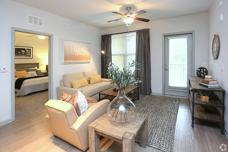 Living room with wood floor with large rug, comfortable leather seating, large side tables, and door to balcony.