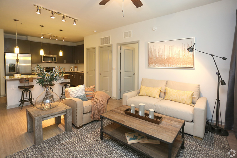 Living room with wood floors with rug, comfortable leather seating, modern coffee table, and freestanding lamp.