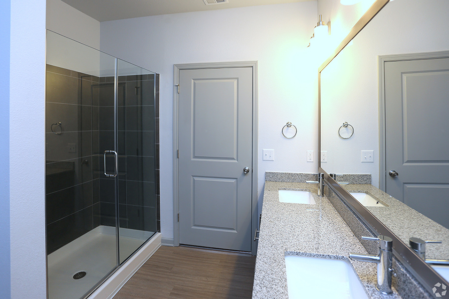 Bathroom with dual sinks, large mirror with lights, and large shower with glass door.