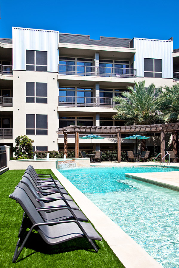Pool area with lounge chairs on grass, wood pergola, and tall palm trees overlooked by apartment balconies.