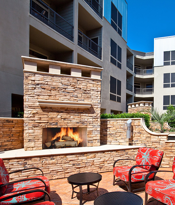 Outdoor seating area with plush outdoor seats and built in stone fireplace.