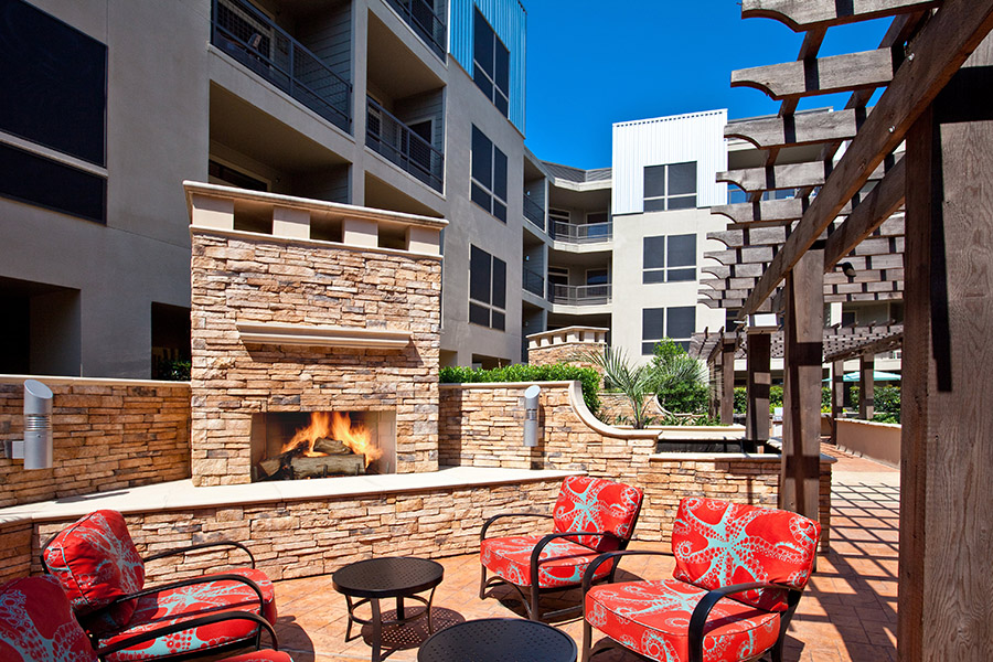 Outdoor seating area with plush outdoor seats, built in stone fireplace, and large wood pergola.
