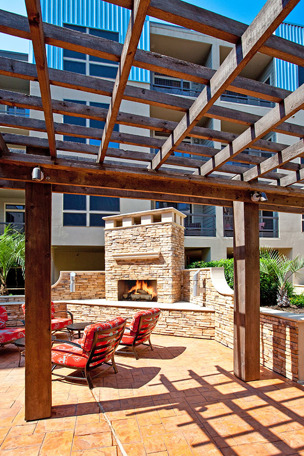 Outdoor seating area with comfortable lounge chairs, large wood pergola, and built in stone fireplace.