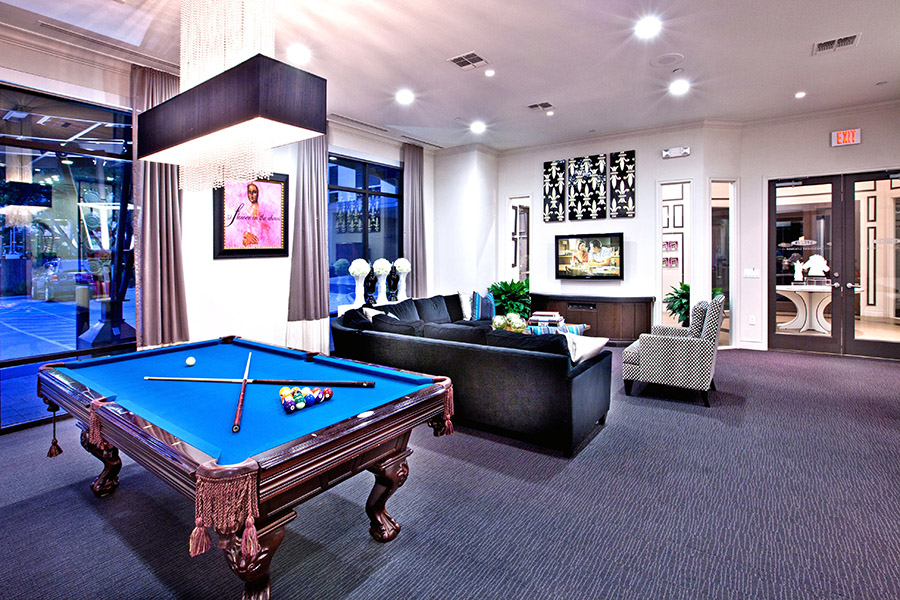 Lounge with carpet, large plush sectional couch, pool table, and large overhead light.