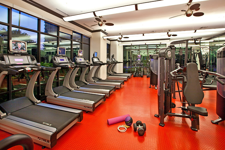 Fitness center with gym floor, weight machines, cardio equipment, and large windows.